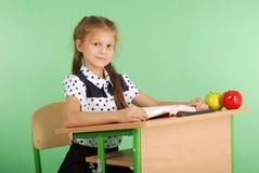 Ragazza in un uniforme scolastico che si siede ad uno scrittorio e che legge un libro Immagine Stock Libera da Diritti