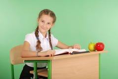 Ragazza in un uniforme scolastico che si siede ad uno scrittorio e che legge un libro Immagine Stock