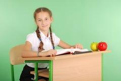 Ragazza in un uniforme scolastico che si siede ad uno scrittorio e che legge un libro Fotografie Stock Libere da Diritti