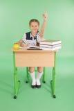 Ragazza in un uniforme scolastico che solleva mano per fare domanda Fotografia Stock
