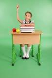 Ragazza in un uniforme scolastico che solleva mano per fare domanda Immagini Stock
