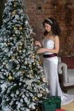 Ragazza in un vestito astuto all'albero di Natale fotografia stock libera da diritti