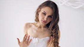 Ragazza in un vestito bianco che si tiene per mano sul vestito archivi video