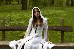 Ragazza in un vestito bianco con un cappuccio di fantasia Fotografie Stock Libere da Diritti