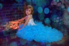 ragazza in un vestito blu da un camino d'ardore Immagine Stock Libera da Diritti
