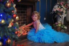 ragazza in un vestito blu da un camino d'ardore Fotografia Stock Libera da Diritti