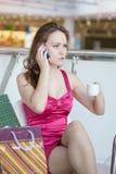 Ragazza in un vestito dentellare con un telefono mobile Fotografia Stock