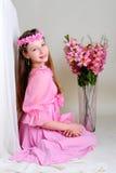 Ragazza in un vestito ed in una corona rosa Fotografia Stock