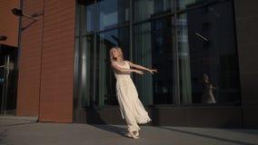 Ragazza in un vestito leggero che balla all'aperto La ballerina sta filando sulla punta dei piedi e sul livello di salto video d archivio