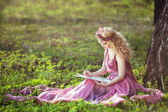 Ragazza in un vestito leggiadramente che si siede sotto un albero nel legno Fotografia Stock Libera da Diritti