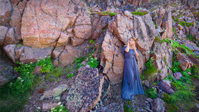 Ragazza in un vestito lungo contro lo sfondo di una roccia Immagini Stock Libere da Diritti
