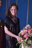 Ragazza in un vestito nero accanto ad un vaso con i fiori Fotografie Stock