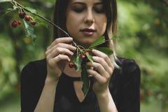 Ragazza in un vestito nero che riunisce un raccolto del ciliegio fotografia stock libera da diritti