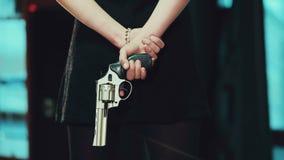 Ragazza in un vestito nero che tiene una rivoltella dietro archivi video