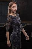 Ragazza in un vestito nero nella stanza di lusso Immagini Stock
