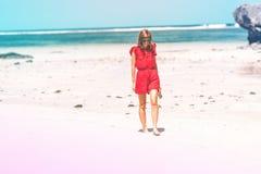 Ragazza in un vestito rosso che cammina a piedi nudi sulla riva di mare Spiaggia tropicale, isola di Bali Giorno pieno di sole Immagini Stock