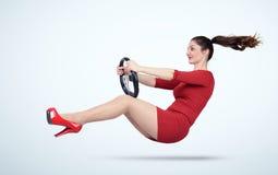 Ragazza in un vestito rosso con un volante dell'automobile immagini stock