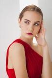 Ragazza in un vestito rosso su un fondo bianco Fotografie Stock