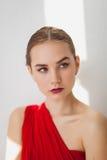 Ragazza in un vestito rosso su un fondo bianco Immagine Stock