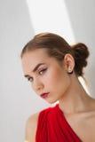 Ragazza in un vestito rosso su un fondo bianco Immagini Stock