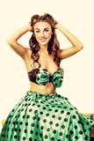 Ragazza in un vestito verde che si siede su un banco Questa immagine assomiglia alla pin-up stilizzata del manifesto immagine stock
