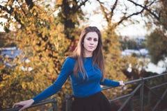 Ragazza in una camicia lunga blu della manica ed in una gonna su una via Autunno fotografia stock