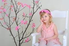 Ragazza in una corona dei fiori in vestito rosa che si siede su uno SMI della sedia Fotografie Stock Libere da Diritti