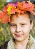 Ragazza in una corona dei fogli di autunno fotografia stock libera da diritti