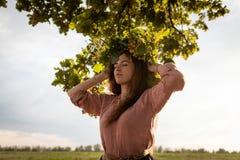 Ragazza in una corona delle foglie della quercia sotto una quercia fotografie stock libere da diritti