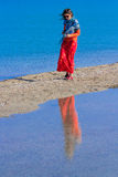 Ragazza in una gonna rossa che cammina sulla sabbia lungo la spiaggia Fotografia Stock