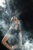Ragazza in una maglietta nera che fuma una sigaretta elettronica che vaping su un fondo nero Fotografia Stock