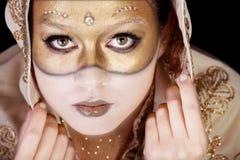 Ragazza in una mascherina di carnevale verniciata sul suo fronte. Fotografie Stock Libere da Diritti