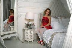 Ragazza in una seduta rossa del vestito Immagine Stock