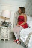 Ragazza in una seduta rossa del vestito Immagini Stock