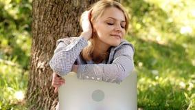 Ragazza vaga che riposa nel parco Donna vaga con il lavoro del computer portatile all'aperto Minuto per il sogno Tecnologia e Int video d archivio