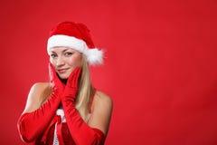 Ragazza vestita come Babbo Natale su una priorità bassa rossa Fotografia Stock
