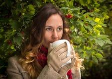 Ragazza in vestiti caldi sul parco di autunno che assaggia una bevanda calda Immagine Stock Libera da Diritti