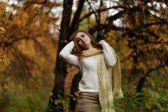 Ragazza in vestiti luminosi contro un fondo dei tronchi di albero nella foresta di autunno fotografie stock libere da diritti