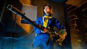 Ragazza in vestiti militari con le pistole con il gioco di stile della precipitazione radioattiva Fotografia Stock Libera da Diritti