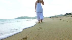 Ragazza in vestito bianco che cammina sulla spiaggia di sabbia il giorno soleggiato Movimento lento archivi video