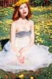 Ragazza in vestito bianco che si siede su una radura dei denti di leone Immagine Stock