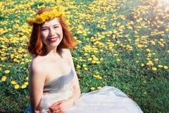 Ragazza in vestito bianco che si siede su una radura dei denti di leone Fotografia Stock Libera da Diritti