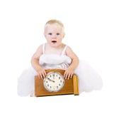 Ragazza in vestito bianco che si siede vicino al vecchio orologio Fotografie Stock Libere da Diritti