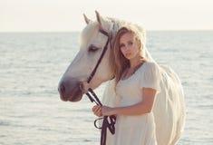 Ragazza in vestito bianco con il cavallo sulla spiaggia Fotografie Stock