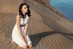Ragazza in vestito bianco sulla sabbia Immagini Stock