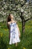 Ragazza in vestito bianco vicino al fiore Immagine Stock