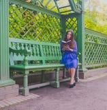 Ragazza in vestito blu che legge un libro che si siede sul banco Fotografie Stock Libere da Diritti