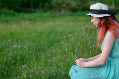 Ragazza in vestito blu che si siede in un campo dei fiori Fotografia Stock Libera da Diritti