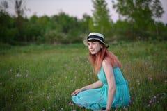 Ragazza in vestito blu che si siede in un campo dei fiori Fotografia Stock