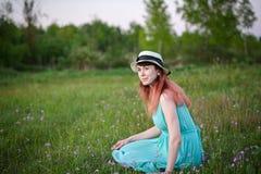 Ragazza in vestito blu che si siede in un campo dei fiori Fotografie Stock Libere da Diritti